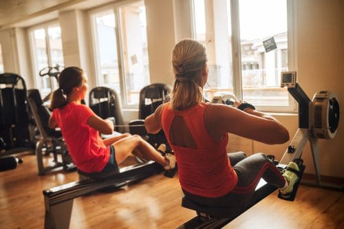 ladies learning how to prevent rowing machine lower back pain